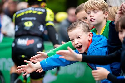 Children waving on the cyclists