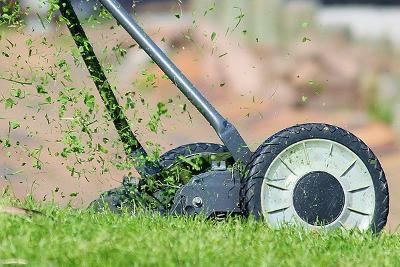 manual lawnmover cutting grass