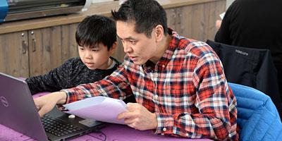 Picture of father and son using tech in Maker Place